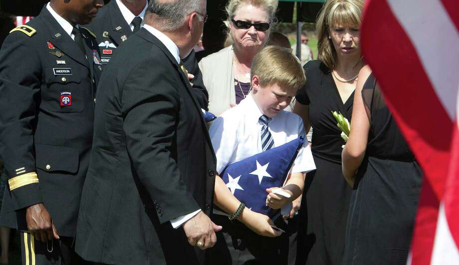 Lt. Col. Roy Tisdale's son Lane Tisdale center, carries a flag as his grandmother Linda Tisdale left, and mother Kim Tisdale right, look on during the burial ceremony for Lt. Col. Tisdale at the Aggie Field of Honor at the City of College Station Memorial Cemetery Thursday, July 5, 2012, in College Station. Lt. Col. Tisdale was shot to death at Fort Bragg by another soldier. Photo: James Nielsen / © Houston Chronicle 2012