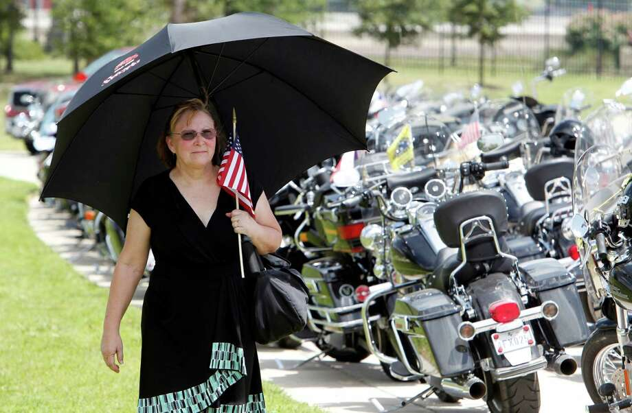 """Pam Johnson of Houston walks past Patriot Guard motor cycles before the burial ceremony for Lt. Col. Roy Tisdale who was shot to death last week at Fort Bragg, at the Aggie Field of Honor at the City of College Station Memorial Cemetery Thursday, July 5, 2012, in College Station. Johnson's son was a member of the Texas A&M Corps of Cadets, Johnson said """"I felt compelled to honor a fellow Aggie today it was the least I could do"""". ( James Nielsen / Chronicle ) Photo: James Nielsen, Houston Chronicle / © Houston Chronicle 2012"""