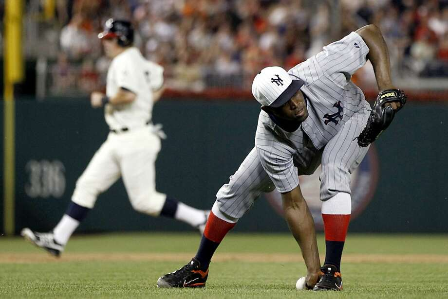 San Francisco Giants relief pitcher Santiago Casilla, right, cannot field a ground ball as Washington Nationals' Tyler Moore runs to third base during the ninth inning of a baseball game, Thursday, July 5, 2012, in Washington. The Nationals won 6-5. (AP Photo/Evan Vucci) Photo: Evan Vucci, Associated Press