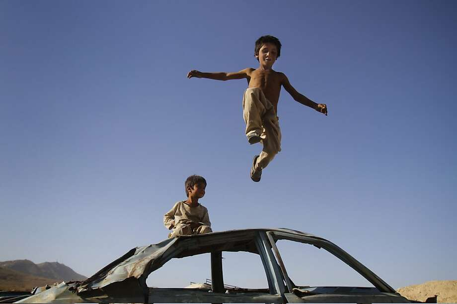 Car hop: In Kabul, a wrecked automobile serves as a playground gym. Photo: Ahmad Jamshid, Associated Press