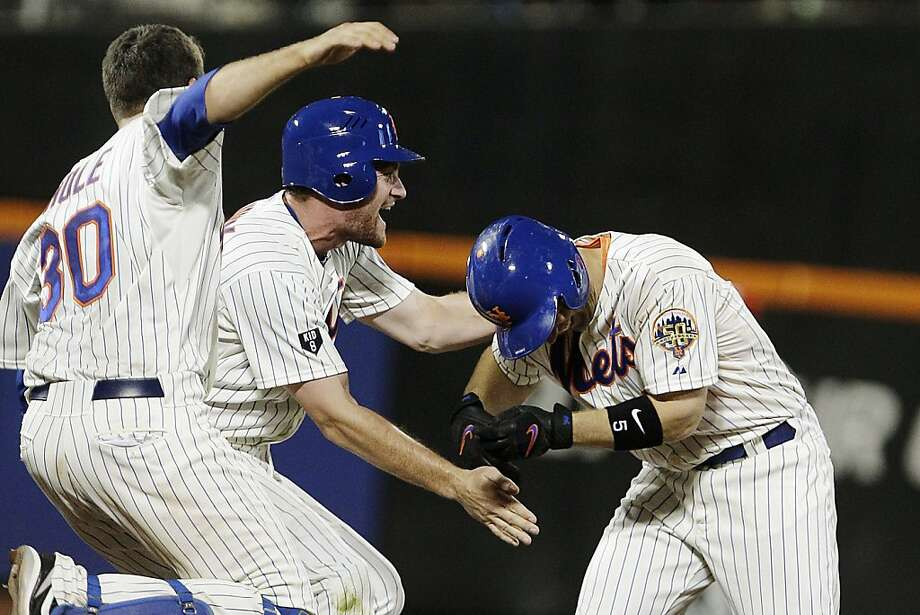 New York Mets' Josh Thole, left, and Daniel Murphy, center, celebrate with David Wright after Wright drove in the game-winning run during the ninth inning of a baseball game against the Philadelphia Phillies, Thursday, July 5, 2012, in New York. The Mets won 6-5. (AP Photo/Frank Franklin II) Photo: Frank Franklin II, Associated Press
