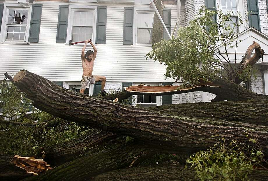 Jack Maxwell works to clear a fallen tree at his neighbor's house that fell during a storm on Thursday, July 5, 2012, in Fort Wayne, Ind. (AP Photo/The Journal Gazette, Swikar Patel)  NEWS-SENTINEL OUT Photo: Swikar Patel, Associated Press