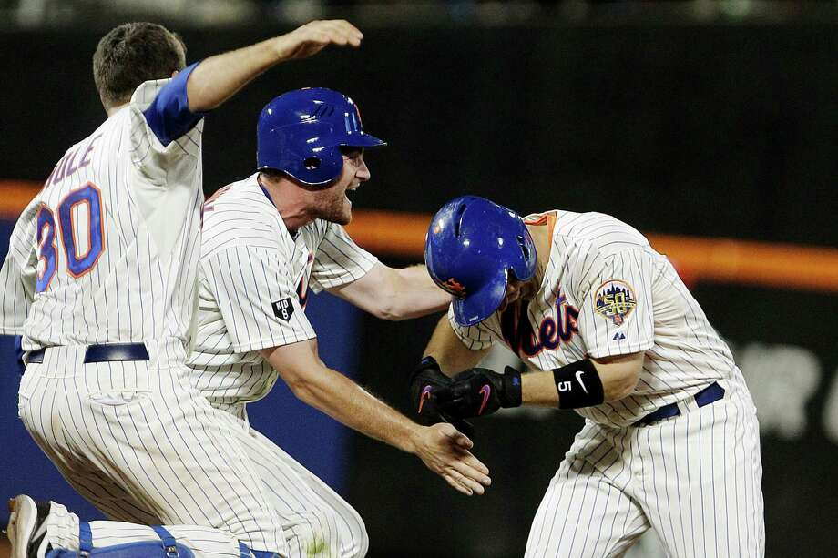 The Mets' Josh Thole, left, and Daniel Murphy, center, celebrate with David Wright after Wright drove in the game-winning run in the ninth of New York's 6-5 win over the Phillies at Citi Field. Photo: Frank Franklin II / AP