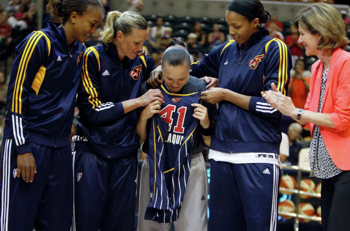 Indianapolis Fever players Tamika Catchings, left, Katie Douglas, and Tammy Sutton-Brown, second from right, presents their former teammate Tully Bevilaqua, center, currently of the San Antonio Silver Stars, a jersey before the tip-off of an WNBA basketball game, Thursday, July 5, 2012, in Indianapolis.