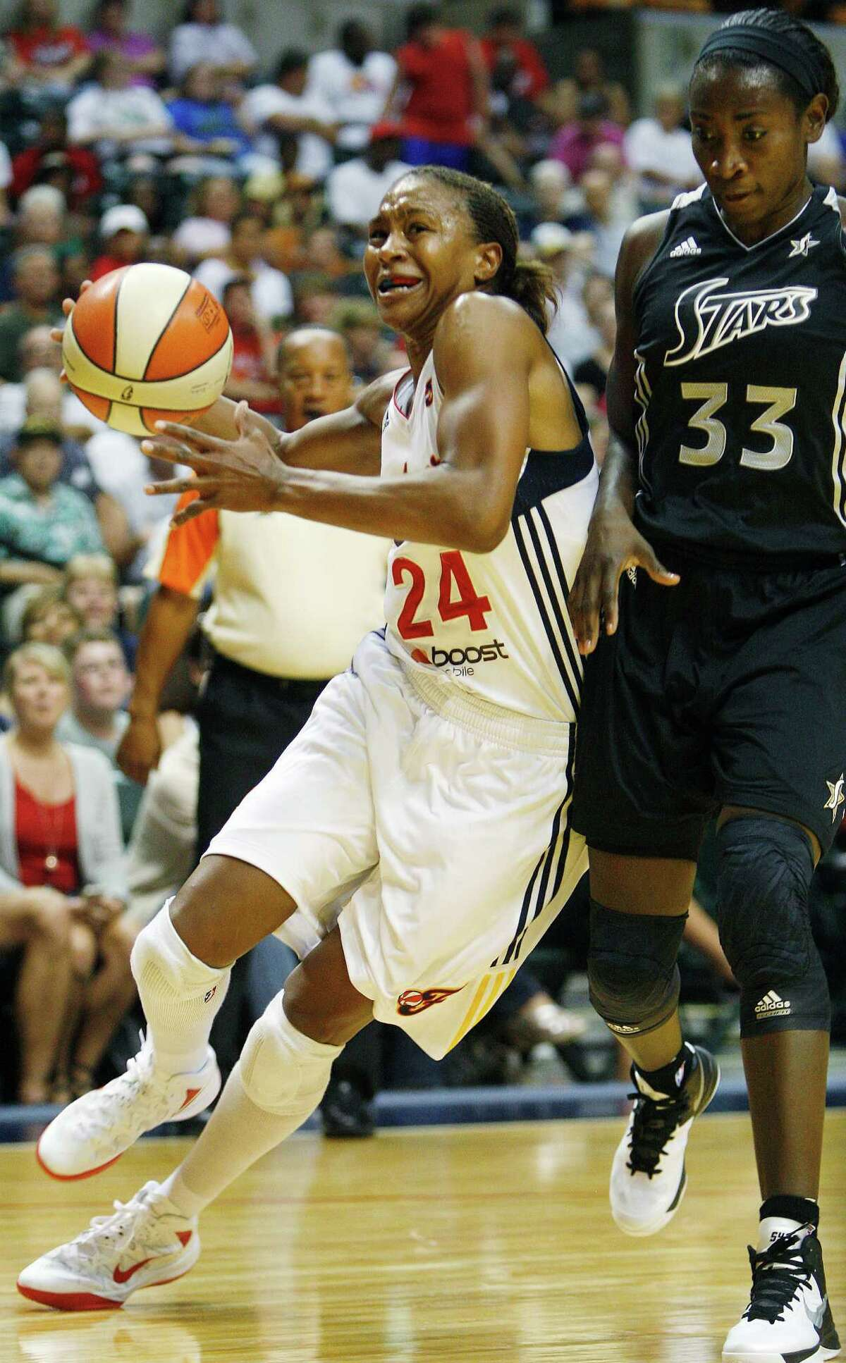 Indiana Fever's Tamika Catchings (24) drives against San Antonio Stars' Sophia Young (33) during the first half of a WNBA basketball game, Thursday, July 5, 2012, in Indianapolis.