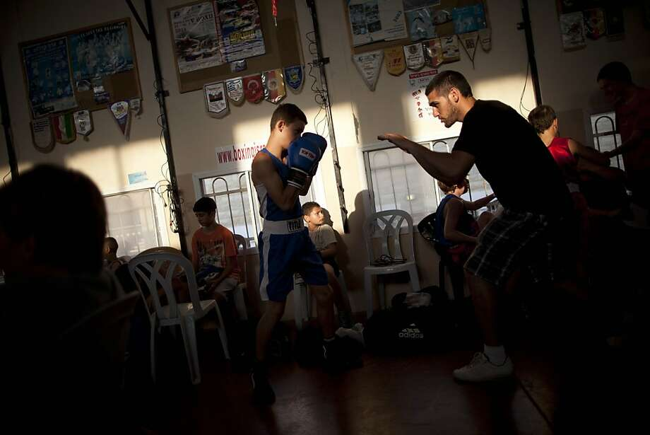 In this picture taken on Thursday, June 28, 2012, Israeli boys warm up prior to a fight during the Israel's National Youth Boxing Championship at the Arab village of Kfar Yasif, northern Israel. Boxing provides a unique chance for young Arab and Jewish competitors to meet in the ring as equals, equipped with helmets and gloves and playing under the same set of rules. (AP Photo/Oded Balilty) Photo: Oded Balilty, Associated Press