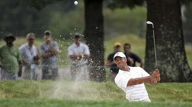 Tiger Woods hits out  bunker on the third hole at The Greenbrier Classic PGA Golf tournament in White Sulphur Springs, W.Va., Thursday, July 5, 2012. Woods finished the day at 1-over 71. (AP Photo/The Roanoke Times, Kyle Green) Photo: Kyle Green, Associated Press