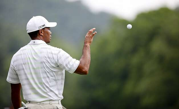 Tiger Woods catches a ball from his caddy during The Greenbrier Classic PGA Golf tournament in White Sulphur Springs, W.Va., Thursday, July 5, 2012. Woods finished the day at 1-over 71.  (AP Photo/The Roanoke Times, Kyle Green) Photo: Kyle Green, Associated Press