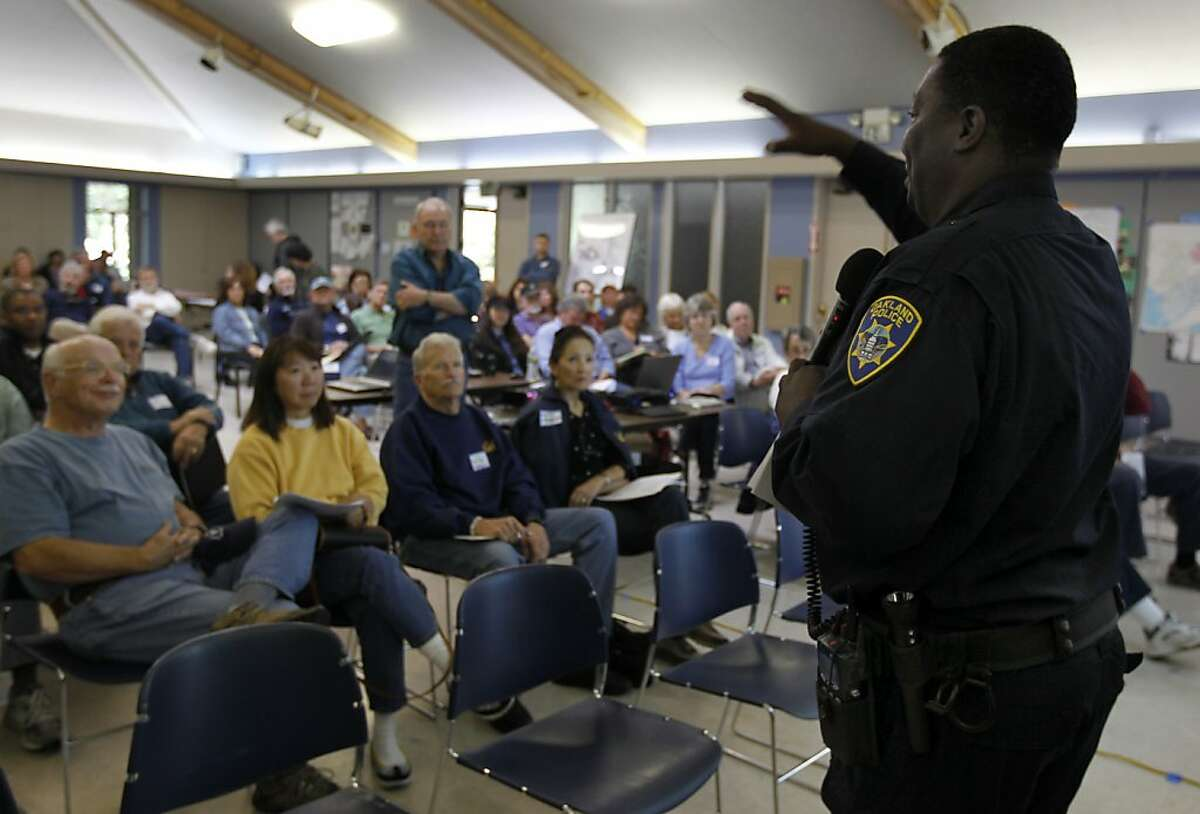 Oakland police services technician Eddie Simlin speaks to a group of residents at a home video surveillance system workshop in Oakland, Calif. on Saturday, June 30, 2012. Concerned with soaring a crime rate, Oakland Hills residents are looking at security cameras as an effective crime-prevention measure.