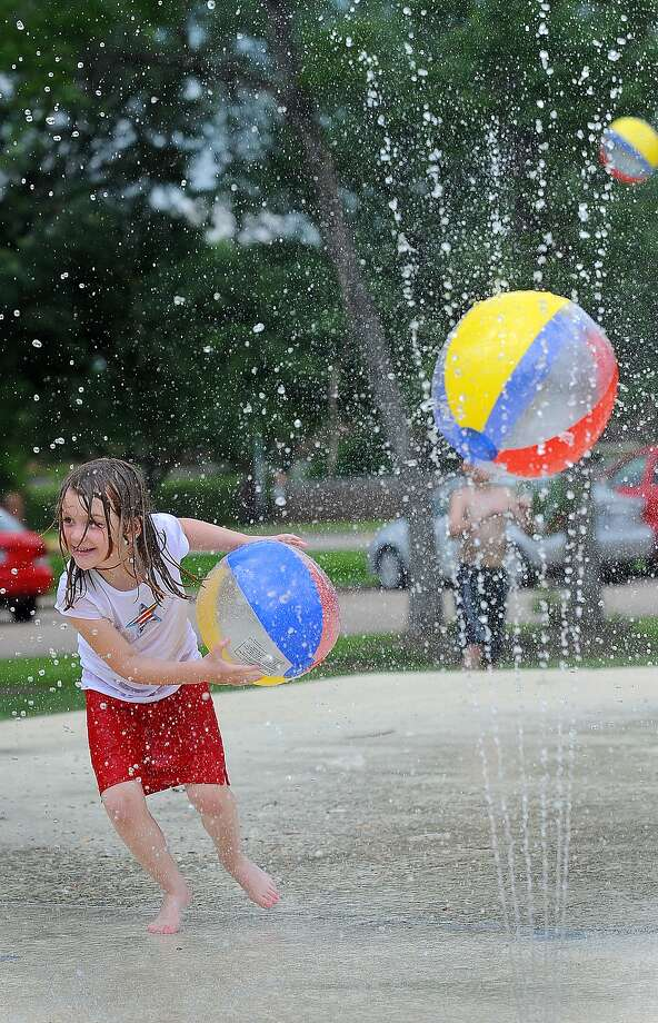 Trying to stay cool, Rebekah Rogers runs through sprays of water at Rogers Park. Guiseppe Barranco/The Enterprise / Beaumont