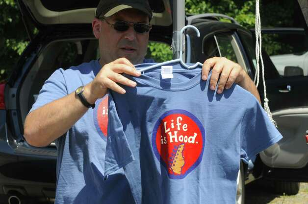 "Vendor Brian Kushner of Long Island hangs one of his self designed shirts, a homage to the Phish song ""Harry Hood"" Friday at the Saratoga Performing Arts Center in Saratoga Springs. (Michael P. Farrell / Times Union) Photo: Michael P. Farrell"