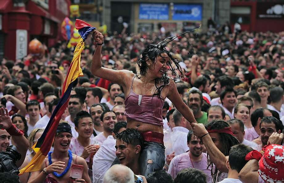 "A reveler carries a young woman on his shoulders in Ayuntamiento square, in Pamplona, northern Spain, Friday, July 6, 2012 during celebrations at the start of Spain's most famous bull-running festival with the annual launch of the ""chupinazo"" rocket. Perhaps best glorified by Ernest Hemingway's 1926 novel ""The Sun Also Rises,"" the San Fermin festival is known around the world for the daily running of the bulls. Photo: Alvaro Barrientos, Associated Press"