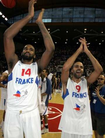 French NBA players Tony Parker, right, and Ronny Turiaf applaud after their Euro 2009 basketball qualifying round France against Belgium, in Pau, southwestern France, Sunday, Aug. 30, 2009. France won  92 to 54 to qualify. (Fred Scheiber / Associated Press)