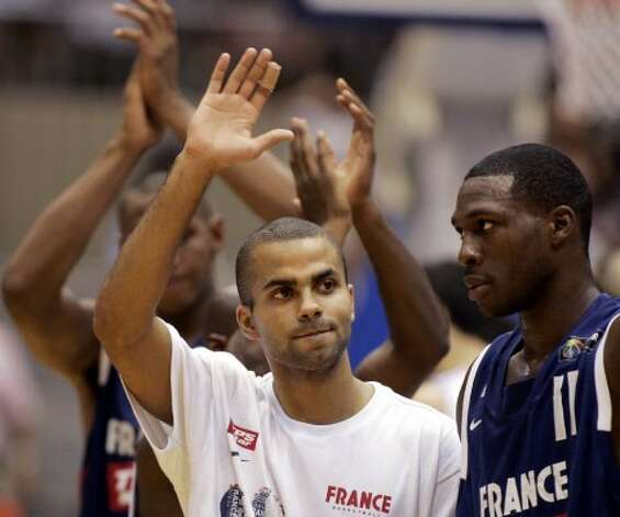 France's Tony Parker, left, waves to fans beside team mate Florent Pietrus after their loss to Argentina in their first round match at the world basketball championships in Sendai August 19, 2006. (Marcos Brindicci / Reuters)
