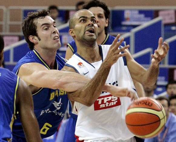French basketball star Tony Parker, right, is blocked by Murilo Becker Da Rosa of Brazil, left,  during the match of the 2006 Stankovic Continental Champions Cup Tuesday Aug. 15, 2006 in Kunshan, China. France won over Brazil 86-74. (Eugene Hoshiko / Associated Press)