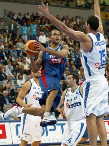 France's Tony Parker, center, who also plays for the San Antonio Spurs, goes for a basket between Greece's Michail Kakiouzis, right, and Theodoros Papaloukas, second from right, during their European basketball championship semi-final match in Belgrade, Serbia and Montenegro, September 24, 2005. (Marko Djurica / Reuters)