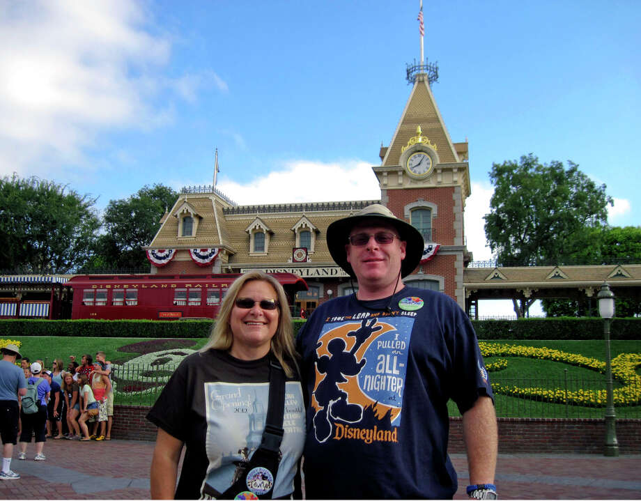 In this Sunday, July 1, 2012, photo, Jeff Reitz and Tonya Mickesh pose for a picture at the halfway point, day 183, in their mission to visit Disneyland in Anaheim, Calif., every day this year. Both were out of work when they decided that instead of moping at home, they would cheer themselves up with a challenge — going to Disneyland all 366 days in 2012. Mickesh now has a full-time job, but Reitz says she still joins him at night. (AP Photo/The Orange County Register, Mark Eades) Photo: Mark Eades, MBO