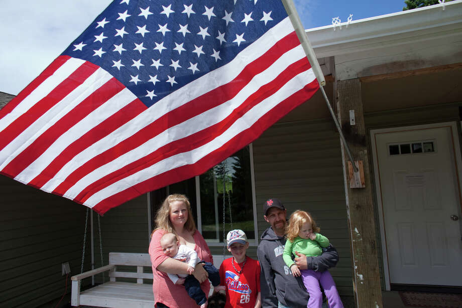 Jessie Bates, left, holds son Samuel, 2 months, as she stands in front of their family home with son Tyler, 11, daughter Jordan, 2, and husband John Bates outside their reconstructed home on the KItsap Peninsula on Friday, June 29, 2012. The family purchased a home at the site that unknown to them previously served as a meth lab. The old house was a toxic mess and family members started to come down with strange ailments before they moved out, tore down the house, rebuilt and became mired in debt. Photo: JOSHUA TRUJILLO / SEATTLEPI.COM