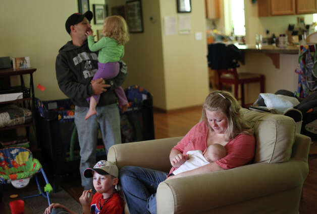 Jessie Bates, bottom right, holds son Samuel, 2 months, as she spends time with, clockswise, son Tyler, 11, husband John Bates and daughter Jordan, 2 in their reconstructed home on the KItsap Peninsula on Friday, June 29, 2012. The family purchased a home at the site that unknown to them previously served as a meth lab. The old house was a toxic mess and family members started to come down with strange ailments before they moved out, tore down the house, rebuilt and became mired in debt. Photo: JOSHUA TRUJILLO / SEATTLEPI.COM