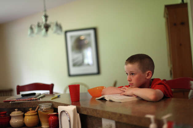 Tyler Bates, 11, relaxes at the kitchen counter in his family's reconstructed home on the KItsap Peninsula on Friday, June 29, 2012. The family purchased a home at the site that unknown to them previously served as a meth lab. The old house was a toxic mess and family members, including Tyler, started to come down with strange ailments before they moved out, tore down the house, rebuilt and became mired in debt. Photo: JOSHUA TRUJILLO / SEATTLEPI.COM