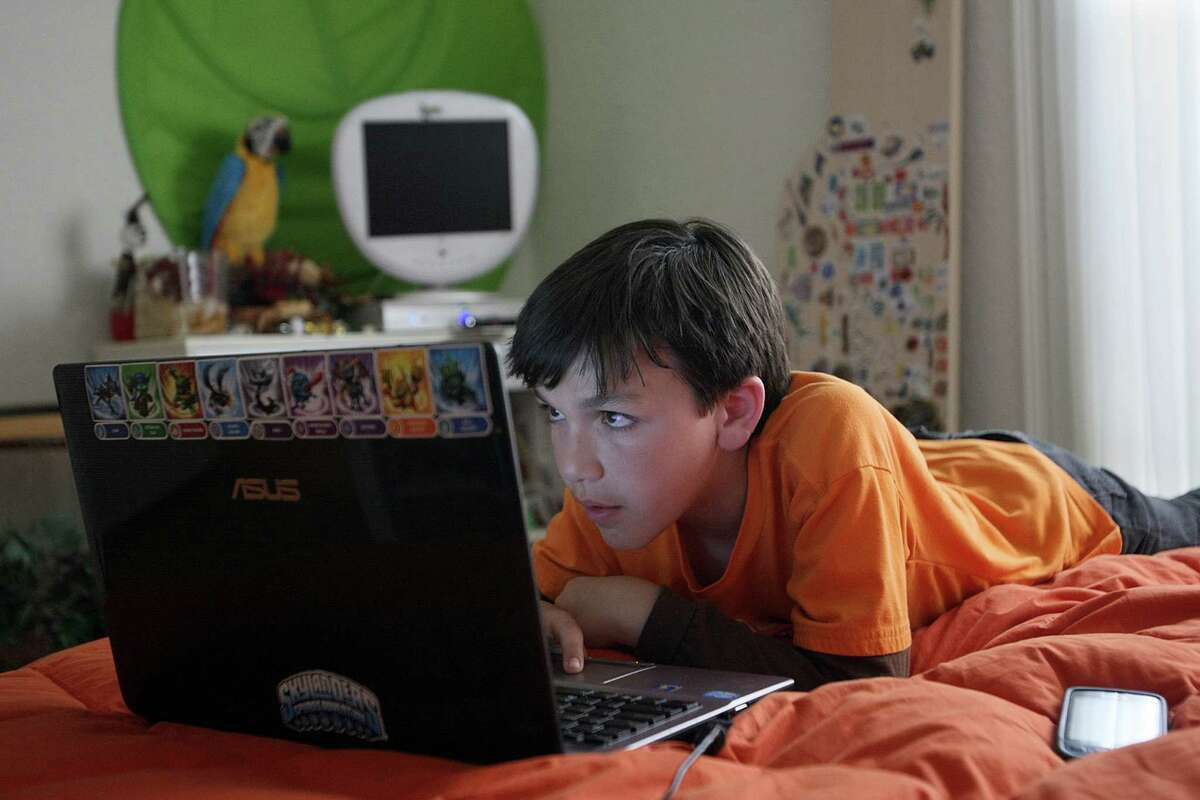 Cole Chanin-Hassman, 10, looks at a computer game called Minecraft on his laptop in his Brentwood home on May 31, 2012. Like many other kids his age, the Los Angeles fourth-grader counts among his entertainment tools his Xbox 360 game console, his Android phone and his computer.