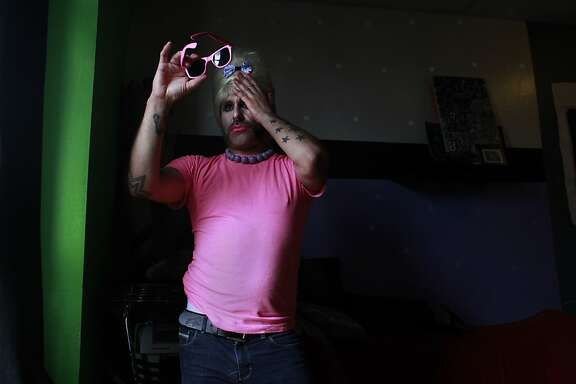 Dressed as Bubbles, Anthony Torres does a last second makeup check before heading out for the day in San Francisco, Calif.