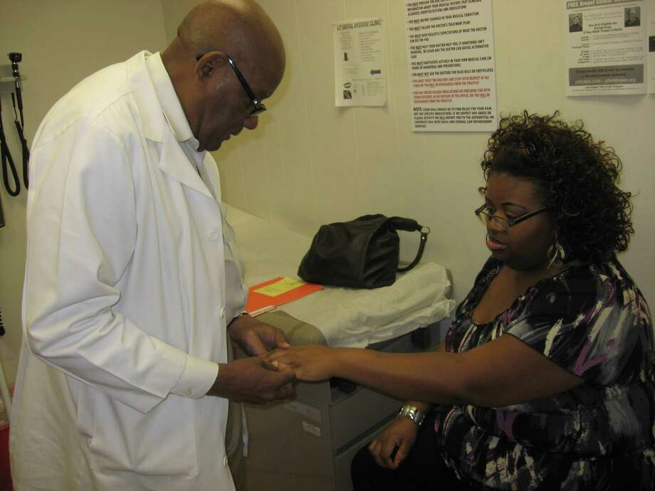 Dr. Cecil Walkes, the Jefferson County Health Authority, examines LaKeisha Sears, who is on disability and has not had health insurance since she was laid off from her job as a manager with quick-service restaurant chain two years ago. Sears is hoping to return to work -- with health insurance -- but for now must depend on visits to the county's health department. Dan Wallach/The Enterprise Photo: Dan Wallach
