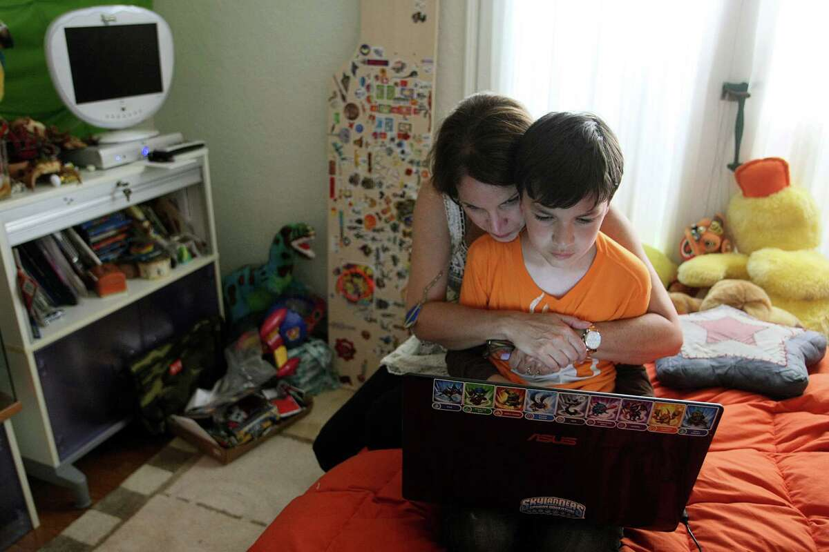 Jeannine Chanin-Penn, left, sits with her son Cole Chanin-Hassman, 10, in Coles bedroom in Brentwood, May 31, 2012. Cole is looking at a computer game call Minecraft on his laptop, a game that teaches him to build cities and other programs. Like many other kids his age, the Los Angeles fourth-grader counts among his entertainment tools his Xbox 360 game console, his Android phone and his computer.