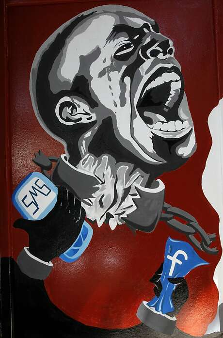 """FILE - In this March 30, 2011, file photo, a mural depicting a man in shackles and the Facebook logo and a mobile phone is seen on the wall of the University of Helwan arts academy in the Zamalek neighborhood of Cairo, Egypt. The team from the CIA's Open Source Center, housed in a unassuming brick building in a Virginia industrial park, pores daily over tweets, Facebook, newspapers, TV news channels, local radio stations, Internet chat rooms _ anything overseas that anyone can access, and contribute to, openly. The center saw the uprising in Egypt coming said the center's director, Doug Naquin. The center already had """"predicted that social media in places like Egypt could be a game-changer and a threat to the regime,"""" he said in a recent interview with The Associated Press.  (AP Photo/Manoocher Deghati, File) Photo: Manoocher Deghati, Associated Press"""