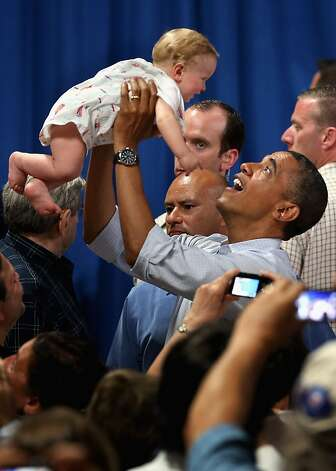 POLAND, OH - JULY 06:  U.S. President Barack Obama lifts 8-month-old Nathan Johnson of Youngstown, Ohio, during a campaign event at Dobbins Elementary School July 5, 2012 in Poland, Ohio. This is the second day of Obama's ''Betting On America'' campaign through Northern Ohio and Western Pennsylvania by bus. The president highlighted his administration?s efforts to improve the economy by creating manufacturing jobs and rescuing the American auto industry and also taking swings at the presumptive Republican presidential nominee, former Governor of Massachusetts Mitt Romney. (Photo by Chip Somodevilla/Getty Images) Photo: Chip Somodevilla, Getty Images