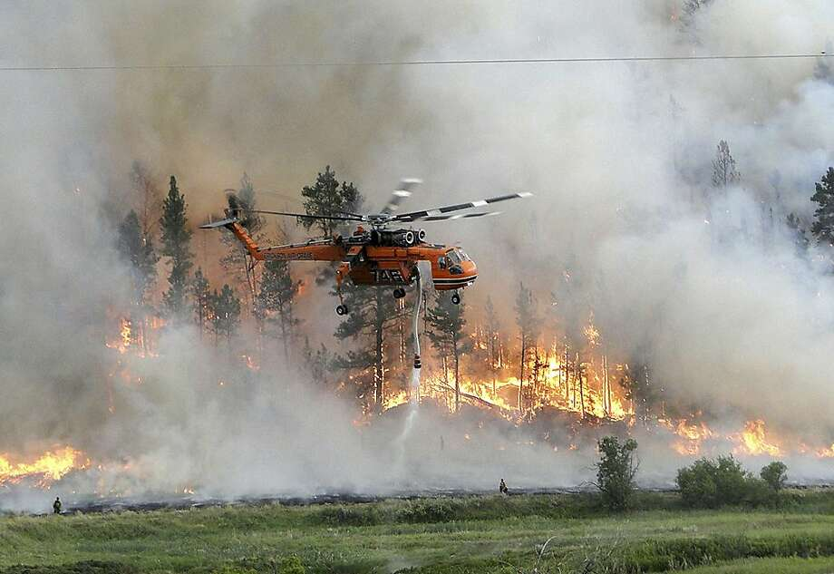 A helicopter drops water as it assists in firefighting efforts at the Taylor Creek fire 25 miles southeast of Ashland, Mont., in this photo made Thursday, July 5, 2012, and released by the U.S. Fish & Wildlife Service.  Fire officials said most of Thursday's fire activity was on the blaze in southeastern Montana, which was fueled by high winds. (AP Photo/U.S. Fish & Wildlife Service, Gerald Vickers) Photo: Gerald Vickers, Associated Press