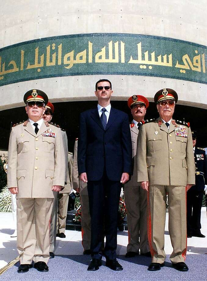 FILE - In this Oct. 6, 2002 file photo, Syrian President Bashar Assad, center, with Syrian Defense Minister Mustafa Tlass, right, and Hassan Turkmany, Chief of Staff, visit the tomb of the unknown soldier, in Damascus, on the occasion of the 29th anniversary of their Liberation War, when Syria and Egypt launched surprise attacks against Israel on Oct. 6, 1973. A top general who has abandoned President Bashar Assad's regime was a longtime friend from Syria's most powerful Sunni family, and his break with the inner circle signals crumbling support from a privileged elite. Brig. Gen. Manaf Tlass was a commander in the powerful Republican Guard and the son of former defense minister Mustafa Tlass, who held the post for 32 years until he retired in 2004.(AP Photo/Sana, File) Photo: Sana, Associated Press