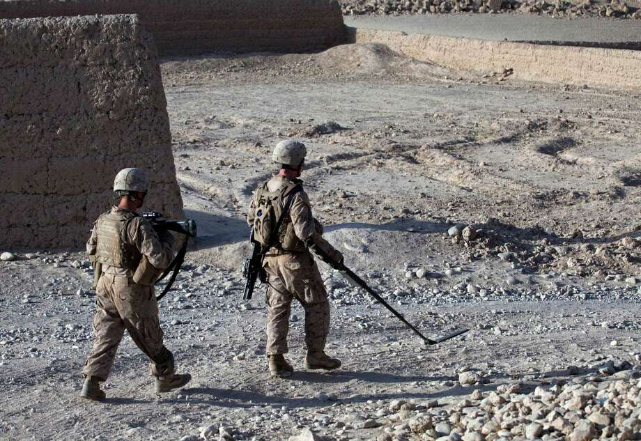 Marines patrol with the help of a metal detector in Afghanistan, where a surge in training and equipment has helped troops avoid homemade bombs. Photo: Brennan Linsley / AP