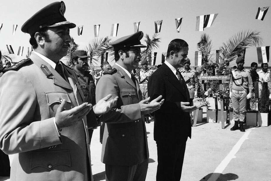 Syrian President Hafez Assad, right, and Brig. Gen. Mustafa Tlass, center, take part in ceremonies in Damascus honoring Syrian dead in this file photo. Tlass, who is reported to have defected and fled the country, was a commander in the powerful Republican Guard and son of a former defense minister. Photo: Uncredited / AP