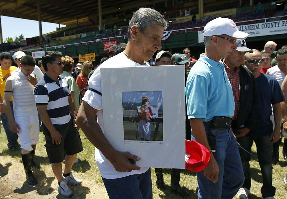 Joe Hernandez carries a portrait of jockey Jorge Herrera, 33, after a trackside moment of silence. Photo: Paul Chinn, The Chronicle