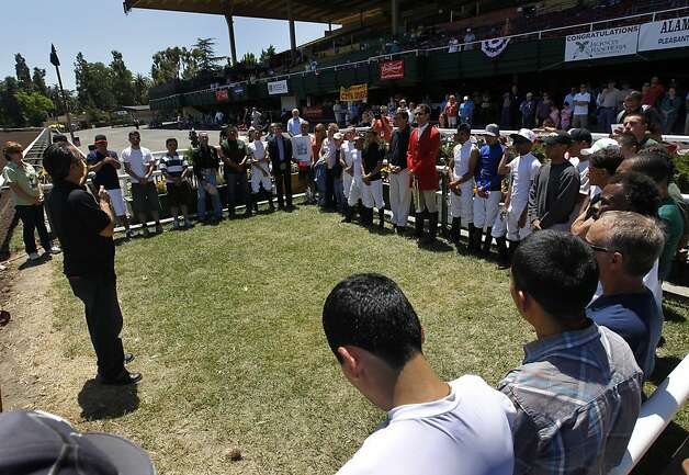 Jockeys and race track employees gather in the winner's circle to pay tribute to Jorge Herrera at the Alameda County Fair in Pleasanton, Calif. on Friday, July 6, 2012. Herrera was the jockey who died while riding Morito in the eighth race on Thursday. Photo: Paul Chinn, The Chronicle