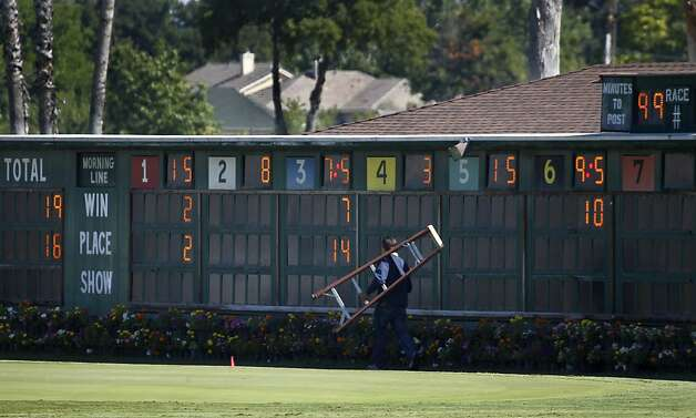 A track employee prepares the scoreboard for the day's thoroughbred races at the Alameda County Fair in Pleasanton, Calif. on Friday, July 6, 2012, one day after jockey Jorge Herrera died when he was thrown from Morito during the final race. Photo: Paul Chinn, The Chronicle