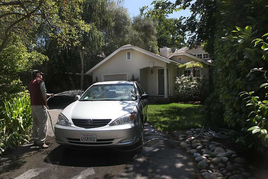 A man hoses off his car at a home in Atherton, where Facebook, with offices in nearby Menlo Park, is helping to fill city coffers. Photo: Liz Hafalia, The Chronicle