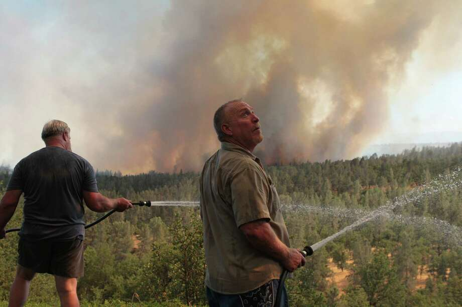 J.R.Kaufman, of Shasta, Calif., left, helps his friend, Walter Robba protect his home  in Redding, Calif., on Thursday, July 5, 2012, as the Dale Fire makes its way north.  Authorities say a 1,200-acre wildfire near Redding is 30 percent contained and has destroyed two outbuildings. Officials say five homes were damaged but firefighters were able to save them all. Photo: Andreas Fuhrmann, Associated Press / The Record Searchlight