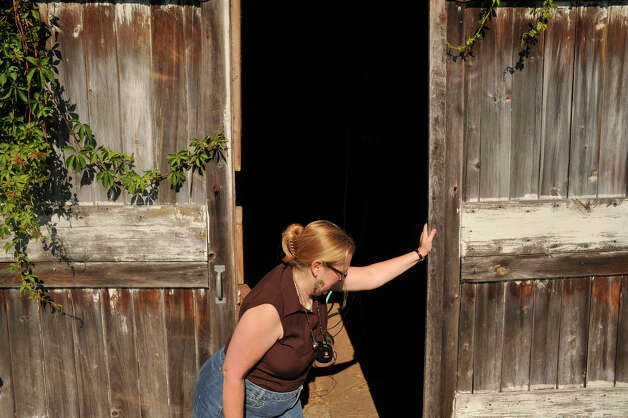 Donna Katsuranis opens the door to a barn at the Eriksen Farm Open Space to turn on the water to irrigate the Brookfield Giving Garden on Friday, July 6, 2012. The Eriksen family deeded the property to the town of Brookfield to have it be used by the public. Photo: Jason Rearick / The News-Times