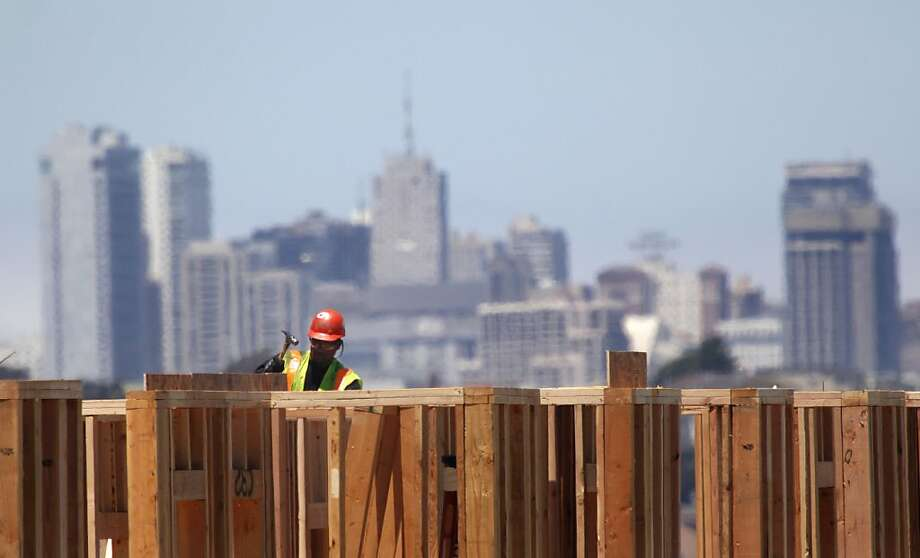A construction worker works against a backdrop of San Francisco at the Hunters View housing project construction site on Friday, July 6, 2012 in San Francisco, Calif. Photo: Lea Suzuki, The Chronicle