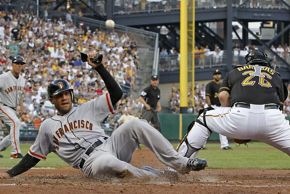 San Francisco Giants' Justin Christian, left, scores on a double to center field by Giants' Ryan Theriot as the throw gets away from Pittsburgh Pirates catcher Rod Barajas during the fourth inning of a baseball game in Pittsburgh, Friday, July 6, 2012. (AP Photo/Gene J. Puskar)