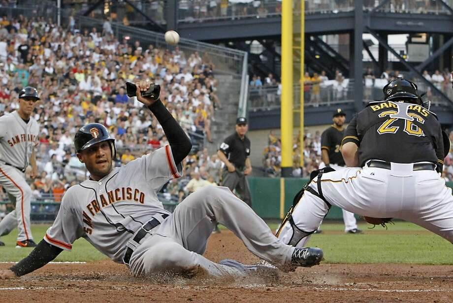 San Francisco Giants' Justin Christian, left, scores on a double to center field by Giants' Ryan Theriot as the throw gets away from Pittsburgh Pirates catcher Rod Barajas during the fourth inning of a baseball game in Pittsburgh, Friday, July 6, 2012. (AP Photo/Gene J. Puskar) Photo: Gene J. Puskar, Associated Press