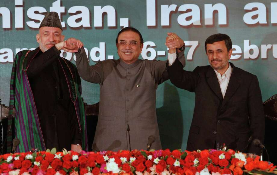 "Pakistan's President Asif Ali Zardari, center, holds the hands of Afghan President Hamid Karzai, left, and Iranian President Mahmoud Ahmadinejad after their joint news conference at the President house in Islamabad, Pakistan on Friday, Feb. 17, 2012. The Afghan president says ""impediments"" in ties between Kabul and Islamabad must soon be removed so that progress can be made in peace talks to end the war in Afghanistan. (AP Photo/B.K. Bangash) Photo: B.K. Bangash / AP"
