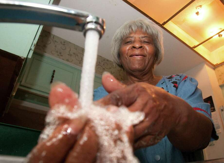 Annie Williams washes up Friday under her kitchen faucet, something she'd been unable to do since last September. Photo: J. Patric Schneider / Houston Chronicle