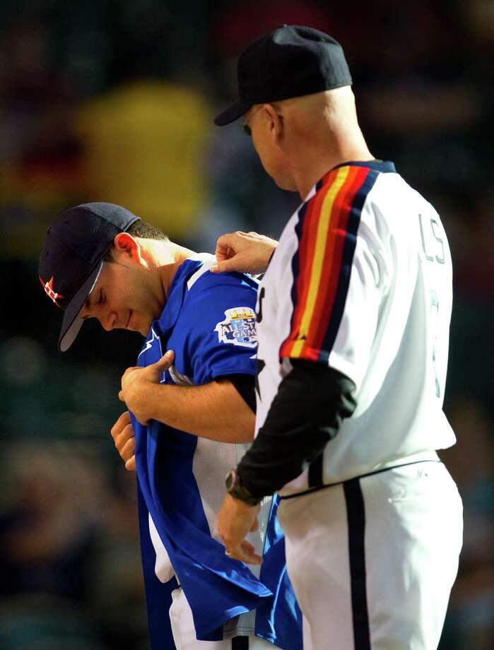 Astros manager Brad Mills, right, helps Jose Altuve try on his All-Star jersey before the game. Photo: Cody Duty / © 2011 Houston Chronicle