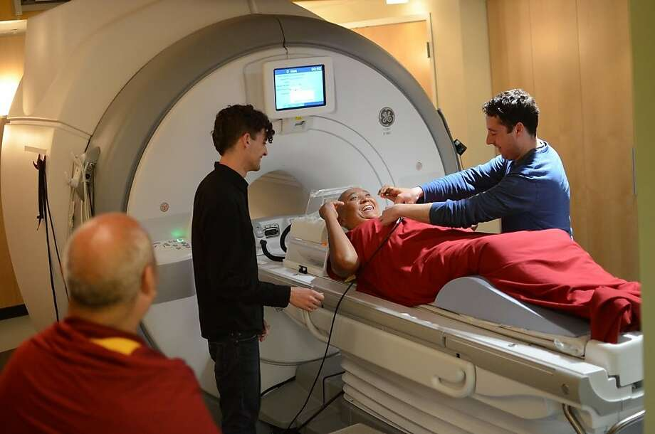 Stanford doctoral researchers Matthew Sacchet (left) and Alex Genevsky (right) prepare a Tibetan monk for a brain scan, as part of a study of the biology of compassion. Photo: Bryce Johnson, Science For Monks