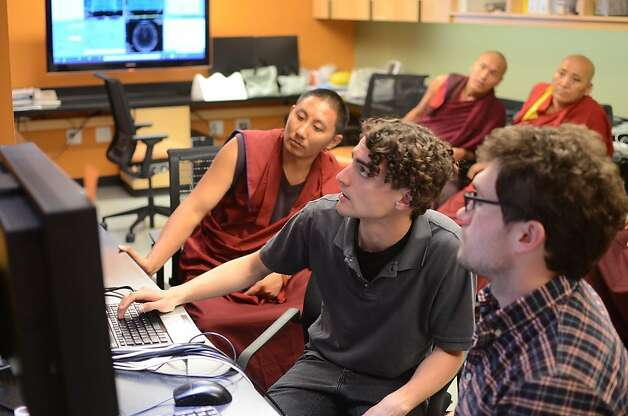 Tibetan monks from India look at brain scans at Stanford, shown to them by neuroscience doctoral student Matthew Sacchet and researcher Kiefer Katovich. Photo: Bryce Johnson, Science For Monks