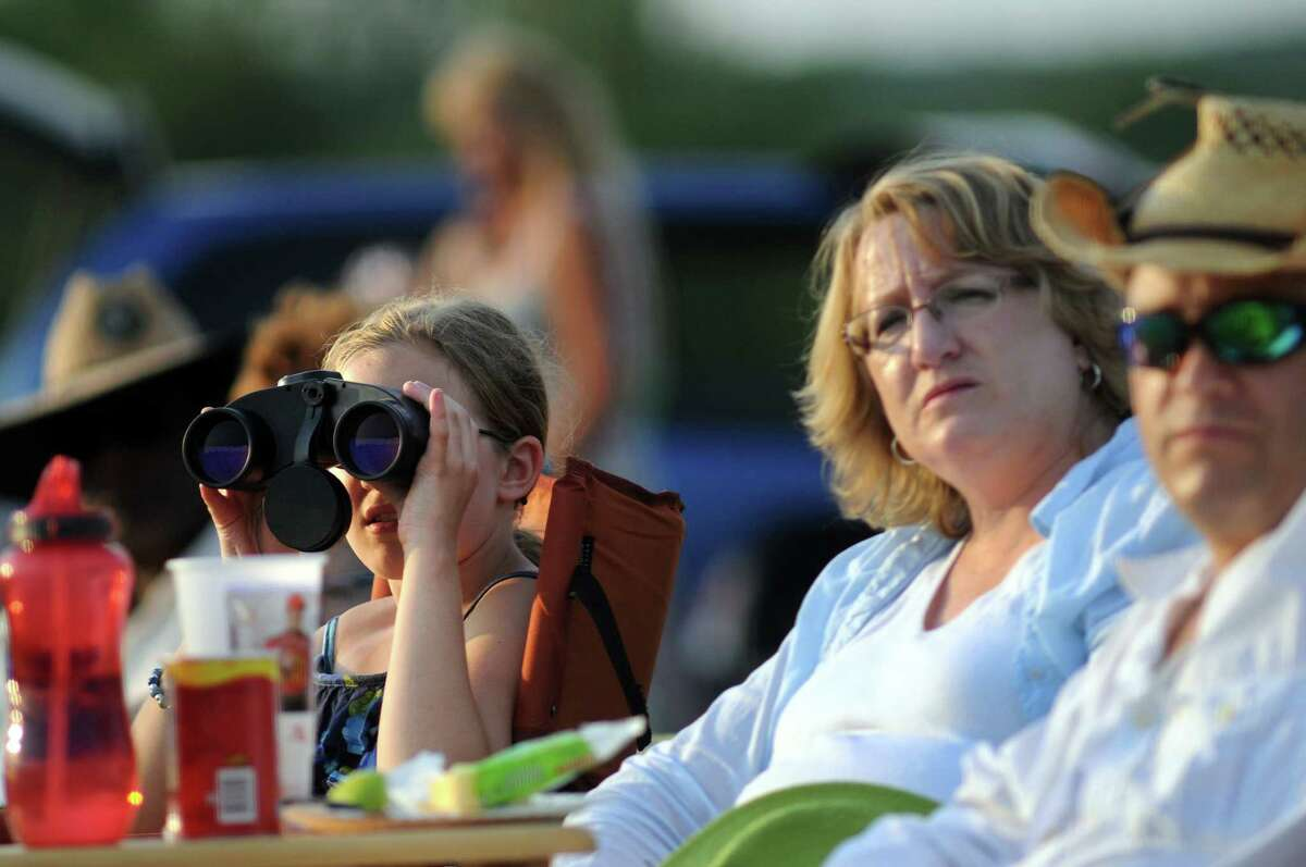 Caroline Koziol, 10, of Halfmoon, left, uses binoculars to watch the polo match on opening day of the Saratoga Polo Association 2012 season on Friday, July 6, 2012, in Greenfield Center, N.Y. (Cindy Schultz / Times Union)