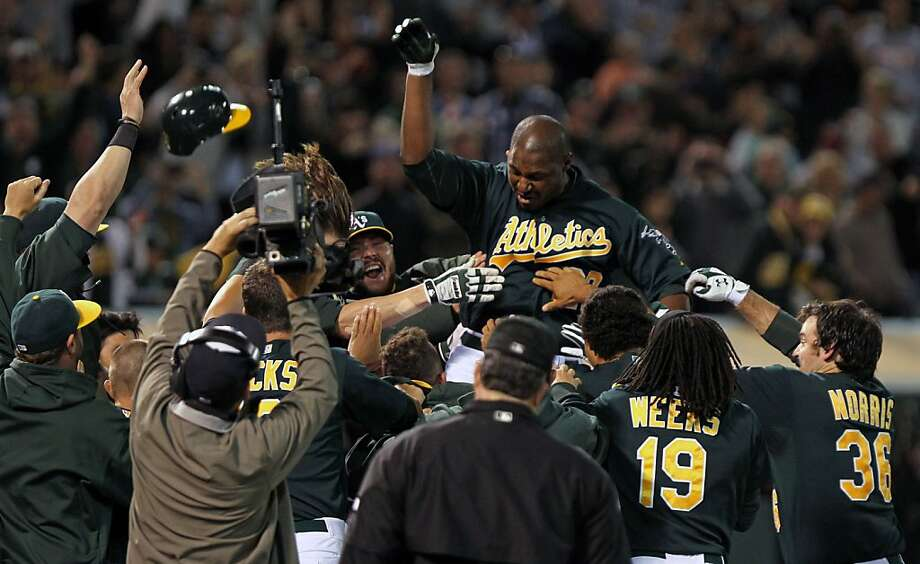 Oakland Athletics Chris Carter jumps on home plate after hitting a three run home run in the bottom of the 11th inning to defeat the Seattle Mariners in their MLB baseball game 4-1 Friday, July 6, 2012, in Oakland California. Photo: Lance Iversen, The Chronicle